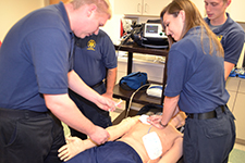 Two paramedics doing chest compressions on a simulation mannequin
