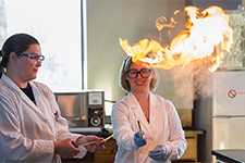 Chemistry professor Dr. Andrea Geyer lights a gas on fire, causing it to shoot out flames