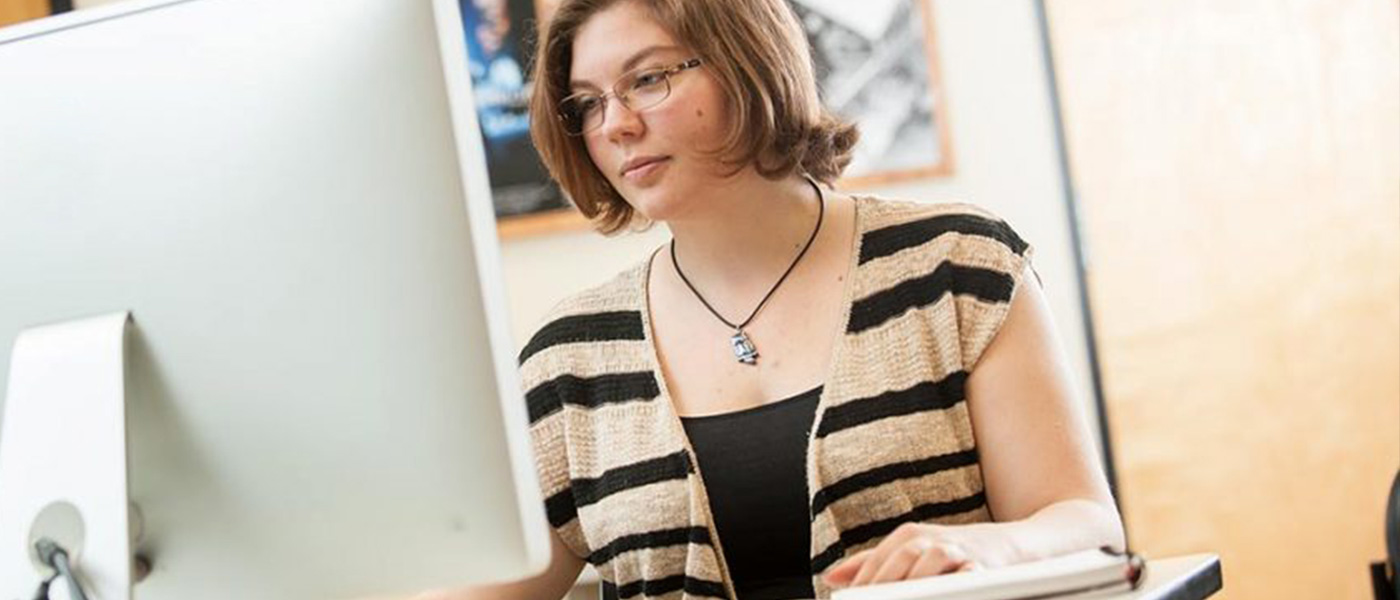 Female USF student researching on a mac computer in the lab.