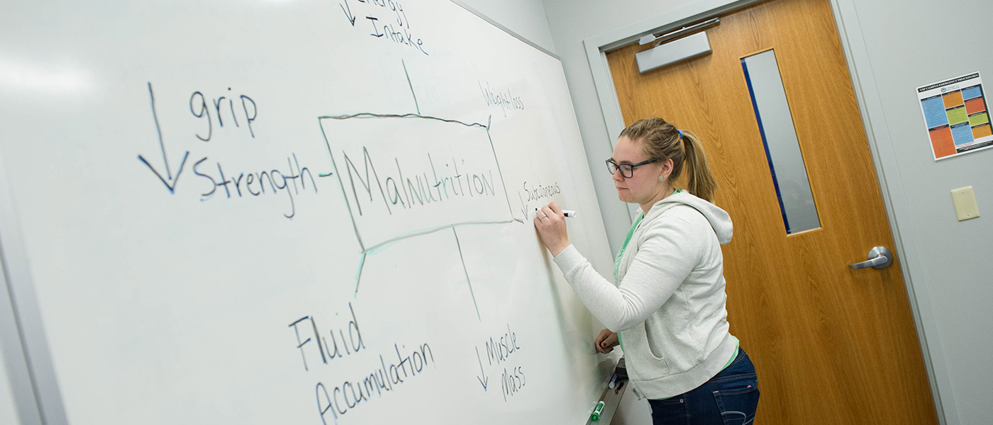 A nutrition student at a whiteboard mapping out signs of malnutrition
