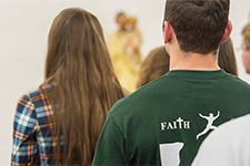The back of a student's shirt says the word Faith