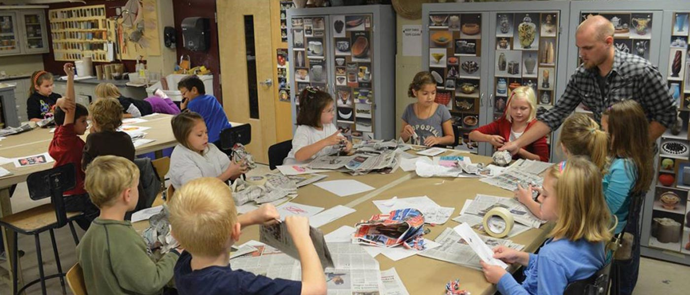 Male student teaching a group of kids how to paper mache.