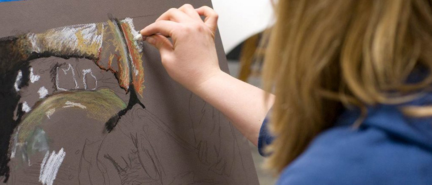 Female USF student working on a oil pastel drawing.